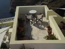 Bästa sikt över en tabell och två stolar som ut ser till havet i Santorini, Grekland royaltyfria bilder