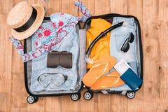 Bästa sikt av öppet bagage mycket av kläder för kvinna` s och andra nödvändiga semesterobjekt Arkivbild