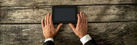 Bästa sikt av affärsmanhänder som rymmer den svarta digitala minnestavlan Royaltyfri Bild