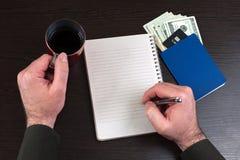 Bästa sikt av affärsmanhandstil på den tomma anteckningsboken kopiera avstånd royaltyfri foto