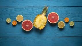 Bästa sikt av ananas och citruns på de blåa träbrädena Royaltyfri Bild