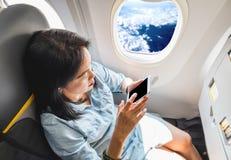 Bästa sikt av asiatiskt kvinnasammanträde på fönsterplatsen i flygplan och t Arkivfoton