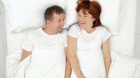 Bästa sikt av att le par som har gyckel i sängnederlag under filten och ser in i kamera stock video