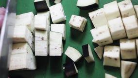 Bästa sikt av aubergine som får snittet in i kuber med den stora kniven på den gröna tabellen arkivfilmer