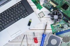 Bästa sikt av bärbar dator- och datorutrustning a på den vita tabellen Arkivfoton