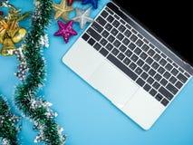 Bästa sikt av bärbara datorn och garneringar på blå isolerad bakgrund Jul och feriebegrepp för nytt år royaltyfri fotografi