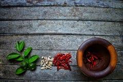 Bästa sikt av bladet och mortlar för gräsplan för citron för vitlök för kryddachilipeppar på bakgrund för stil för tappningträtab royaltyfri bild