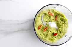 Bästa sikt av blandaren och blandad guacamole med chilipeppar Begrepp av det förberedelse avokado-baserade doppet i köket arkivbilder