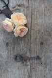 Bästa sikt av blommor och gammal tangent på trägolv Royaltyfria Bilder