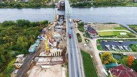 Bästa sikt av brokonstruktion på område med två kranar närliggande väg och flod stock video