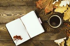 Bästa sikt av dagboken, en kopp av varmt kaffe, hösteksidor och rönnbär på en träbakgrund kopiera avstånd cozy arkivfoto