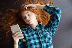 Bästa sikt av damen som ligger och lyssnar till musik arkivfoton
