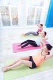 Bästa sikt av damer som gör abs på idrottshallen Fotografering för Bildbyråer