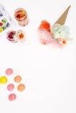 Bästa sikt av dekorativa blommor med makron och frukt- coctailar Arkivfoto
