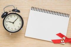 Bästa sikt av den öppna anteckningsboken med klockan på wood bakgrund Arkivfoton