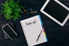 Bästa sikt av den öppna anteckningsboken som är skriftlig med den START-UP inskriften Grön blomma, minnestavla, kulör gemmar, sma arkivfoton