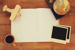 Bästa sikt av den öppna tomma anteckningsboken och och tomma fotografiramar för polaroid bredvid koppen kaffe över trätabellen or Arkivbild