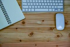 bästa sikt av den arbetande skrivbordtabellen med tangentbordet, mus, anteckningsbok arkivfoto