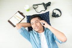 Bästa sikt av den asiatiska mannen som ligger på golvet med bärbara datorn, kamera, ta Arkivfoton