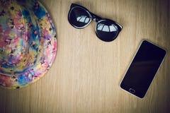 Bästa sikt av den ferieobjekt, hatten, exponeringsglas och telefonen Arkivfoton