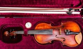 Bästa sikt av den gamla fiolen med pilbågen i rött sammetfall Royaltyfri Foto