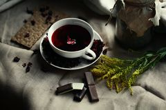 Bästa sikt av den glass koppen för vitt porslin av röd tekarkade på kanfasbordduk Hemlagade choklade kakor, citron arkivfoton