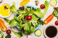 Bästa sikt av den gröna sunda salladbunken med dressingen och ingredienser, slut upp Banta att äta, vegetarian- eller strikt vege Arkivfoton