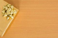 Bästa sikt av den guld- gåvaasken på tabellen med fritt utrymme Arkivfoton
