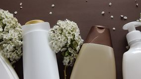 Bästa sikt av den hygieniska/kosmetiska produkten och blommor på brun bakgrund Wellnessskönhetbehandling stock video