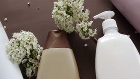 Bästa sikt av den hygieniska/kosmetiska produkten och blommor på brun bakgrund Wellnessskönhetbehandling arkivfilmer