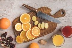 Bästa sikt av den klippta apelsiner, ingefäran och granatäpplet med hemlagade fruktsafter Royaltyfri Fotografi