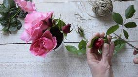 Bästa sikt av den kvinnliga dekoratören som ordnar rosor på trätabellen arkivfilmer