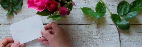 Bästa sikt av den kvinnliga dekoratören som rymmer ett kort som ordnar rosor på trätabellen, begrepp - fiorist, ockupation, hobby arkivfoton