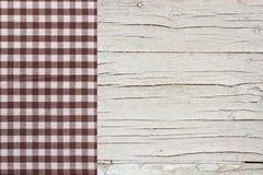 Bästa sikt av den rutiga bordduken på den vita trätabellen Arkivfoton