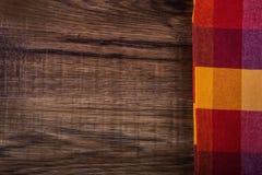 Bästa sikt av den rutiga servetten på trätabellen Arkivbild