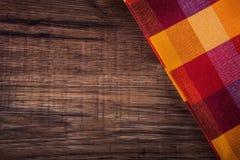 Bästa sikt av den rutiga servetten på trätabellen Fotografering för Bildbyråer