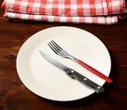 Bästa sikt av den rutiga servetten på trätabellen med plattan och cutl Arkivfoton