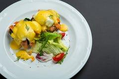 Bästa sikt av den sunda frukosten med tjuvjagad äggroyale, benedict med laxen och grön sallad på svart Royaltyfria Bilder