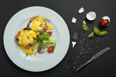 Bästa sikt av den sunda frukosten med tjuvjagad äggroyale, benedict med laxen och grön sallad på svart Royaltyfri Bild
