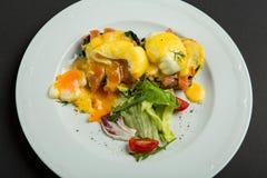 Bästa sikt av den sunda frukosten med tjuvjagad äggroyale, benedict med laxen och grön sallad på svart Arkivbilder