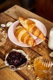 Bästa sikt av den sunda frukosten med två giffel och honungmarmelad och att mjölka på trätabellen arkivbilder