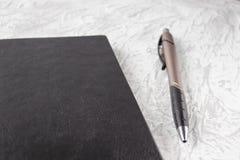 Bästa sikt av den svarta anteckningsboken och pennan på vit skrivbordbakgrund för modell fotografering för bildbyråer