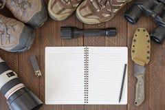 Bästa sikt av den tomma anteckningsboken med smutsiga fotvandra skor, ficklampa, Royaltyfria Foton