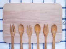 Bästa sikt av den träbestick, skeden och gaffeln på skärbräda arkivbild