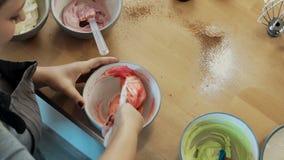 Bästa sikt av den unga blonda kvinnan som blandar krämen för att dekorera och färg i bunken Kvinnliga matlagningmuffin stock video