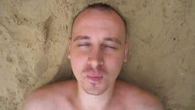 Bästa sikt av den unga mannen som blåser upp bubblor som ligger på stranden stock video