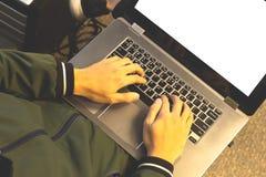 Bästa sikt av den unga upptagna arbetaren som skriver tangentbordet på bärbara datorn royaltyfri foto