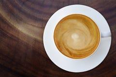 Bästa sikt av den varma kaffecappuccinokoppen med tefatet på wood textur royaltyfri foto
