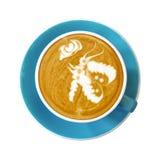 Bästa sikt av den varma kaffelattekoppen på det blåa tefatet med fjäril l royaltyfri bild
