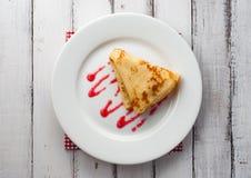 Bästa sikt av den vikta pannkakan på den vita plattan Arkivfoton